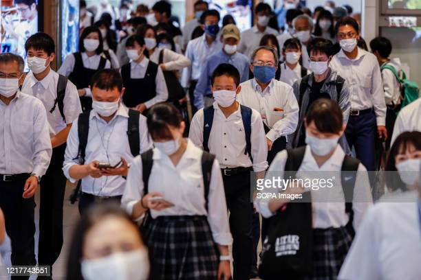 Students wearing face masks as a preventive measure make their way through Tokyo's Kamata Station Japan has lifted a state of emergency imposed due...
