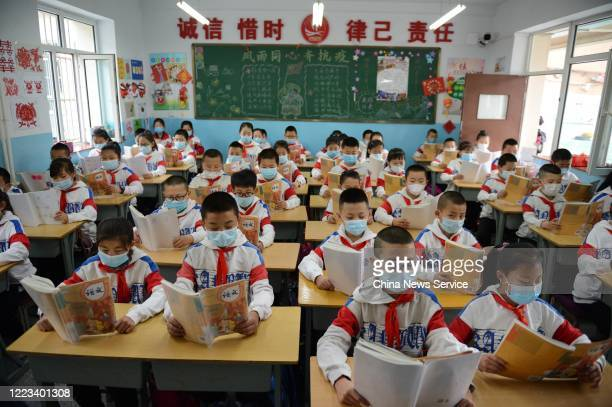 Students wearing face masks have a class at a primary school on May 7, 2020 in Huhhot, Inner Mongolia Autonomous Region of China. A part of primary...