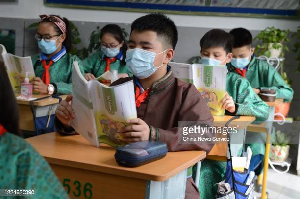 Students wearing face masks have a Mongolian language class at a Mongolian primary school on May 13, 2020 in Ordos, Inner Mongolia Autonomous Region...