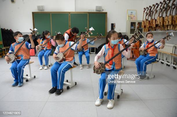 Students wearing face masks play Sanxian, a three-stringed plucked instrument, during music lessons at a Mongolian primary school on May 13, 2020 in...