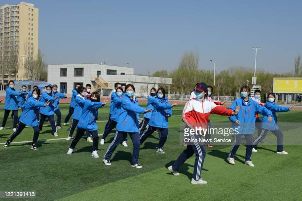 Students wearing face masks play Tai Chi during a physical education class at No.One Middle School on April 27, 2020 in Huhhot, Inner Mongolia...