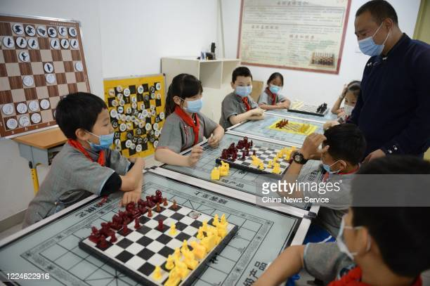 Students wearing face masks play the Mongolian chess at a Mongolian primary school on May 13, 2020 in Ordos, Inner Mongolia Autonomous Region of...