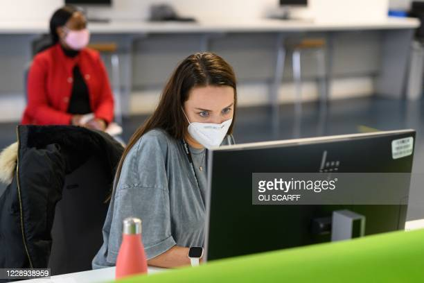 Students, wearing face masks to help mitigate the spread of the novel coronavirus COVID-19, work on computers in the Social Learning Zone at the...