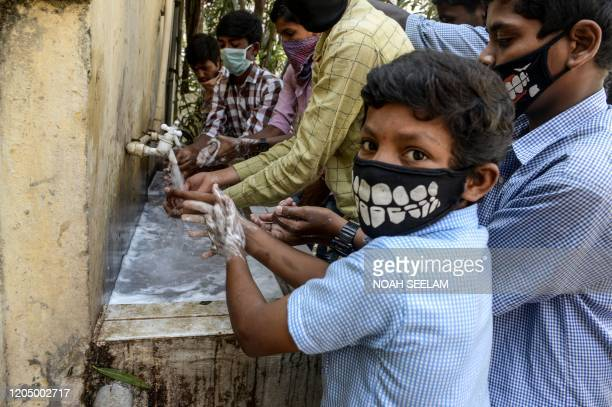TOPSHOT Students wearing facemasks wash their hands before attending a class at a governementrun high school in Secunderabad the twin city of...