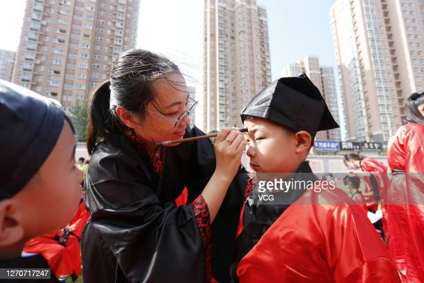 Students wearing Han costumes take part in a first writing ceremony a traditional education activity for children who will start their school life in...