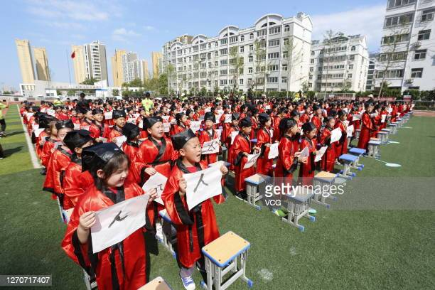 Students wearing Han costumes take part in a first writing ceremony, a traditional education activity for children who will start their school life...