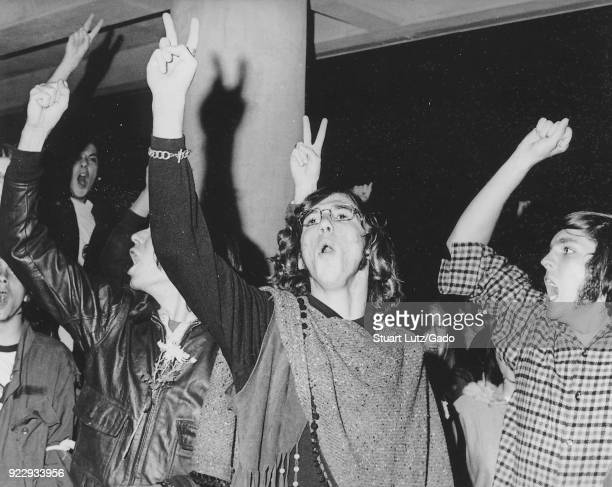 Students wearing hippie attire including one student with long hair and a poncho hold their fingers aloft in a peace sign gesture with some wearing...