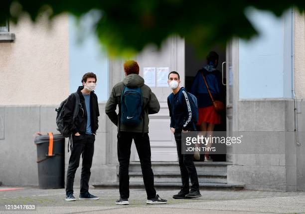Students wearing protective mask stand at distance in the courtyard at the re-opening of the Institut Saint Boniface Parnasse highschool in Ixelles...