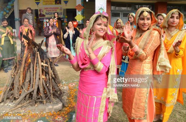 Students wearing traditional Punjabi outfits perform a folk dance to celebrate Lohri, the spring festival, in Amritsar on January 13, 2021.