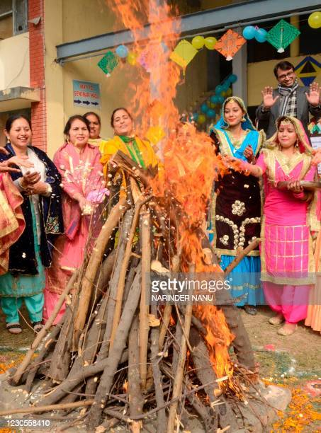 Students wearing traditional Punjabi outfits perform a ritual around a bonfire to celebrate Lohri, the spring festival, in Amritsar on January 13,...