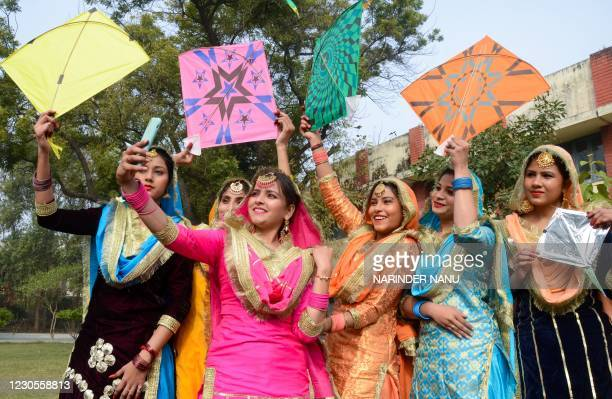 Students wearing traditional Punjabi outfits take selfies as they celebrate Lohri, the spring festival, in Amritsar on January 13, 2021.