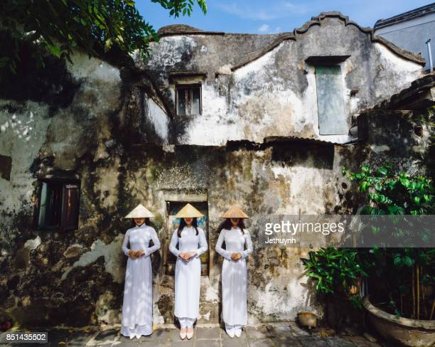 Students wearing Vietnamese Ao Dai sitting in front of old wall in Ancient town Hoi An, Vietnam