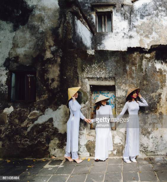 Students wearing Vietnamese Ao Dai standing at old wall in Ancient town Hoi An, Vietnam