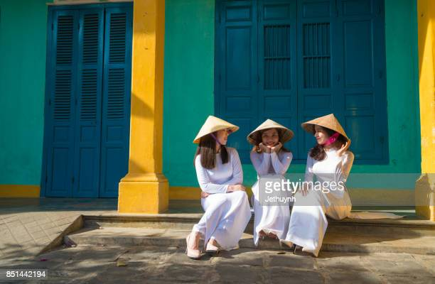 Students wearing Vietnamese Ao Dai walking in front of a house in Ancient town Hoi An, Vietnam
