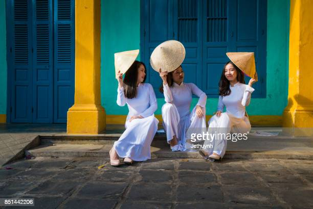 students wearing vietnamese ao dai walking in front of a house in ancient town hoi an, vietnam - traditionally vietnamese stock pictures, royalty-free photos & images