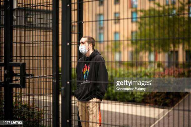 Students who are self-isolating stand behind the security fencing of theoir accommodation as they are interviewed by a television crew on September...