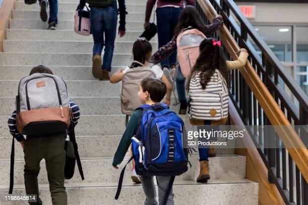 schüler mit rucksäcken klettern haupttreppe ersten schultag - staatliche schule stock-fotos und bilder