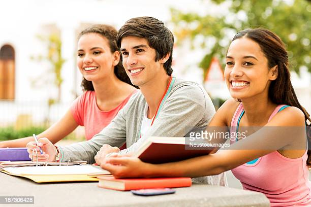 Students With Books And Ring Binder Looking Away On Campus