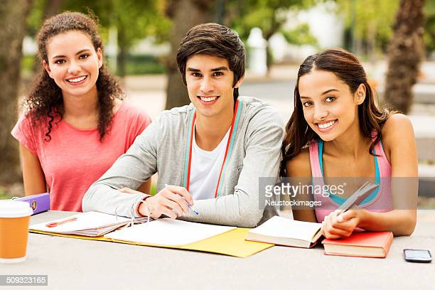 Students With Books And Ring Binder Sitting On College Campus