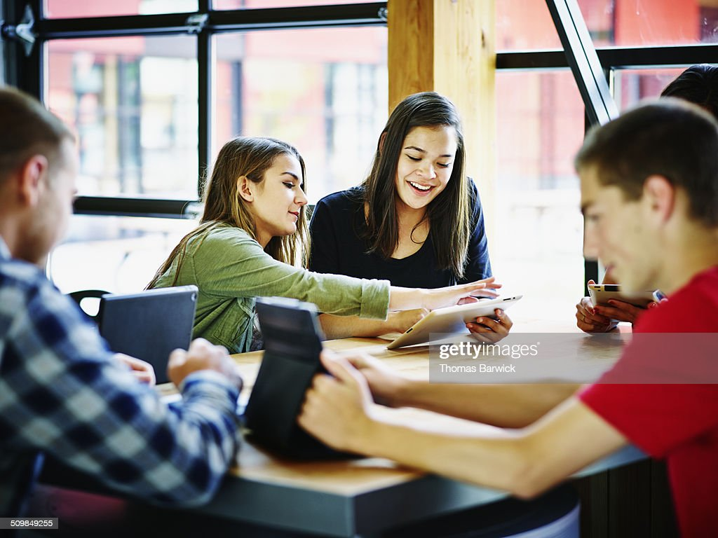 Students with digital tablets in school commons : Stock Photo