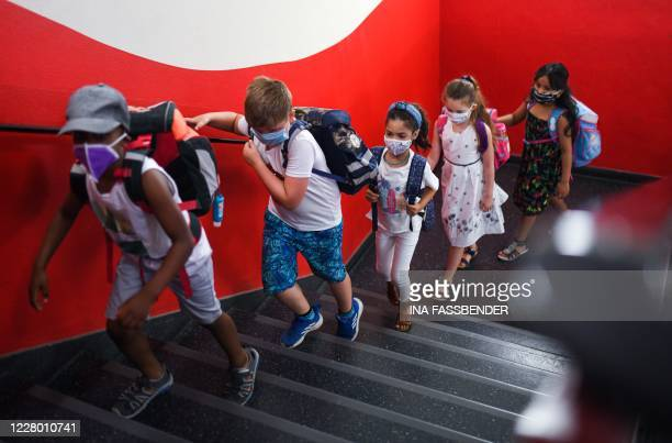Students with face masks go upstairs to their classrooms at the Petri primary school in Dortmund, western Germany, on August 12 amid the novel...