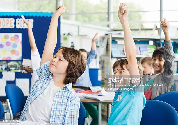 students with hands raised in classroom - human age stock pictures, royalty-free photos & images