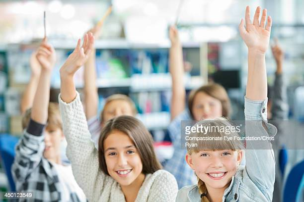 students with hands raised in classroom - hand raised stock pictures, royalty-free photos & images