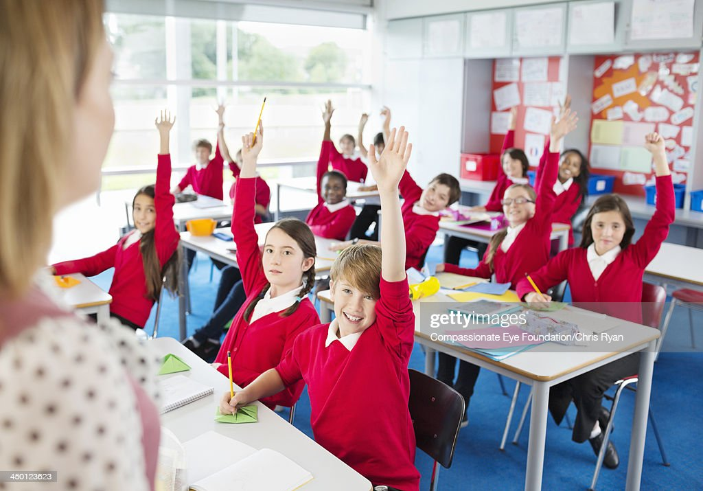 Students with hands raised in classroom : Stock Photo