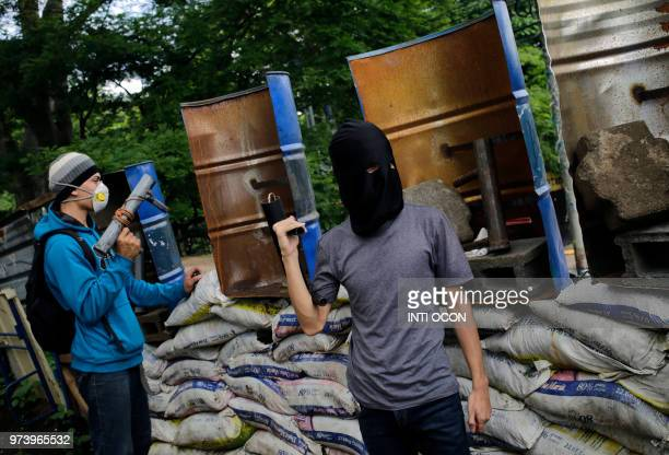 TOPSHOT Students with homemade mortars stand guard behind makeshift shields and barricades at the National University occupied by protesters for over...