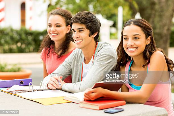 Students With Ring Binder And Books Looking Away On Campus