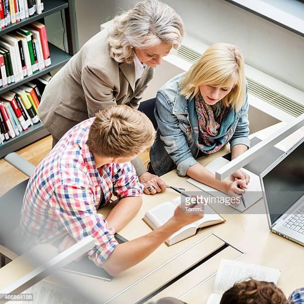 Estudiantes con el profesor de aprendizaje de la biblioteca