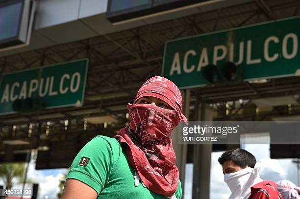 Students with their faces covered take control of the tollbooth on the highway between Acapulco and Mexico DF during a protest demanding the...