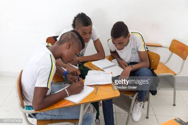 Students work together during class in a catholic school in the neighborhood in El Vergel in Cali in Colombia