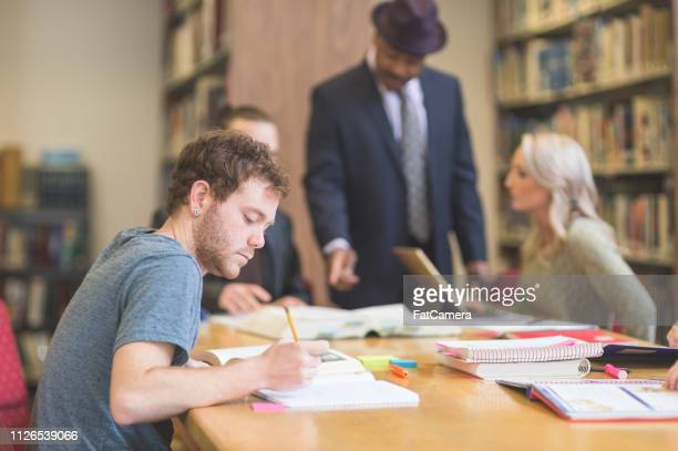students working in a college library - master's degree stock pictures, royalty-free photos & images