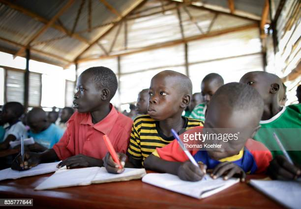 Students write in their school notebooks during the lesson School at Rhino Refugee Camp Settlement in northern Uganda Here children of local people...