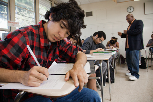 Students writing in classroom - gettyimageskorea