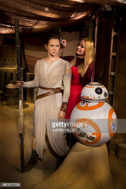 A studio artist puts the finishing touches to a wax figure of Star Wars character 'Rey' played by British actress Daisy Ridley during a photocall at...