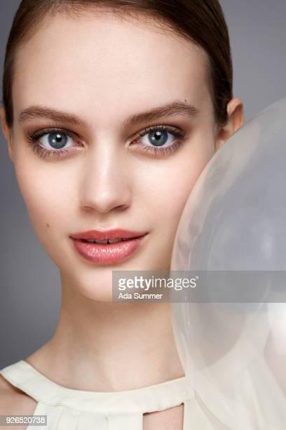 studio beauty shot of a woman holding a balloon to her face - faltenreduktion stock-fotos und bilder