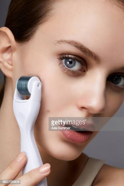 studio beauty shot of a woman holding a needle massage roller to her cheek - acupuncture needle stock pictures, royalty-free photos & images