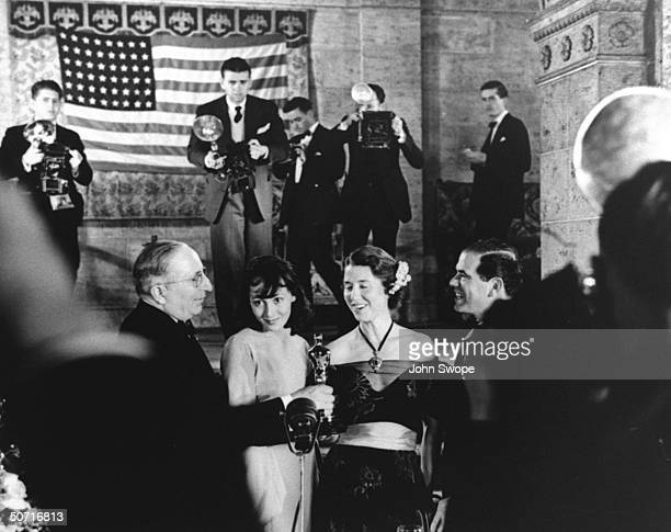 MGM studio chief Louis B Mayer actress Luise Rainer unidentified and director Frank Capra during Academy Awards presentation as photographers work in...