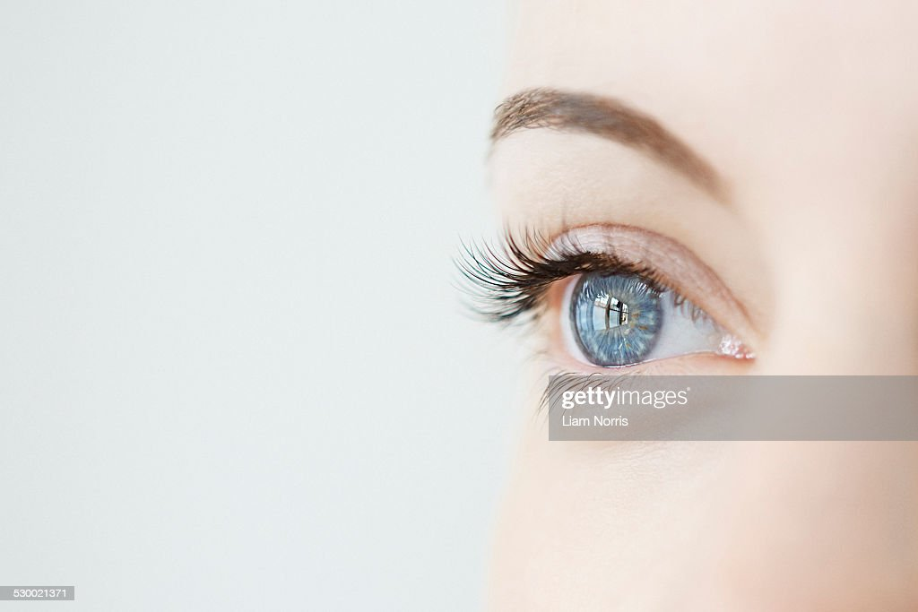 Studio close up of mid adult womans gazing blue eye : Foto de stock