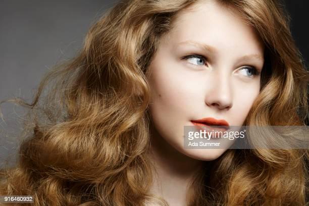 studio close up shot of a beautiful woman with long wavy dark blonde hair