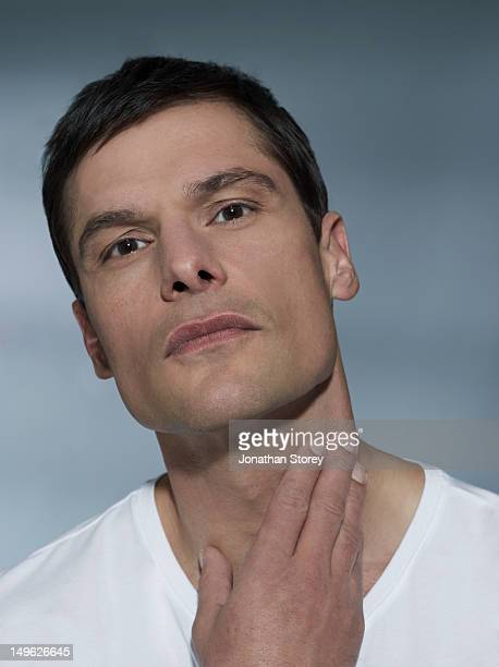 studio close up shot of male touching his neck - shaved stock pictures, royalty-free photos & images