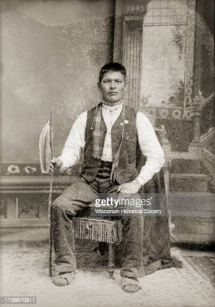 Studio fulllength portrait of a HoChunk man with short hair posing sitting in front of a painted backdrop Black River Falls Wisconsin 1885 Identified...