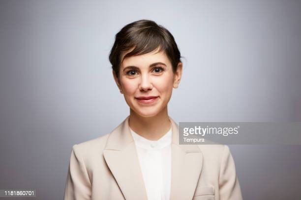 studio headshot of a businesswoman on a gray background. - beige suit stock pictures, royalty-free photos & images