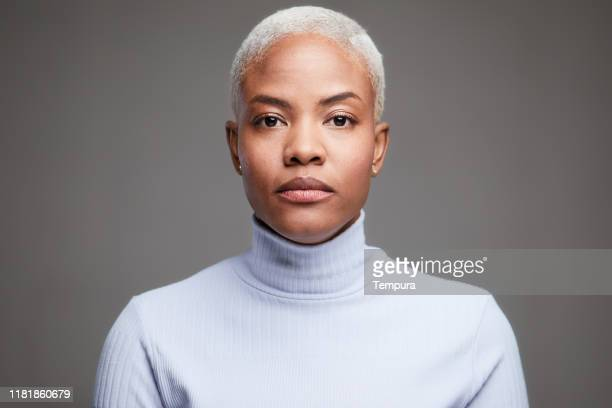 studio headshot of a hispanic woman wearing a turtle neck pullover. - serious stock pictures, royalty-free photos & images