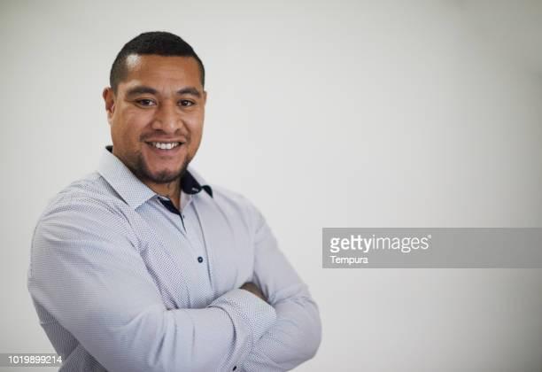 Studio headshot of Pacific Islander man on grey background.