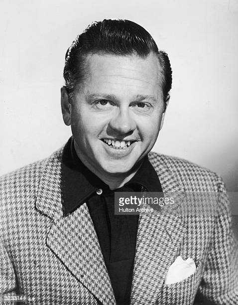 Studio headshot portrait of American actor Mickey Rooney smiling at the camera Rooney is wearing a houndstooth blazer with his hair slicked back