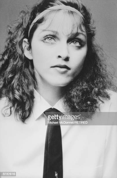 A studio headshot portrait of future American pop singer Madonna looking upwards wearing a white shirt with a dark tie New York City She is wearing a...