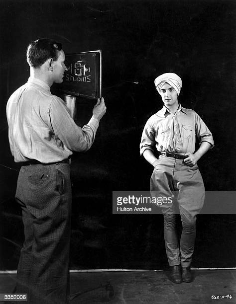A studio lighting technician positions the spotlight on actor Ramon Novarro hearthrob star of the new MGM film 'Son of India'